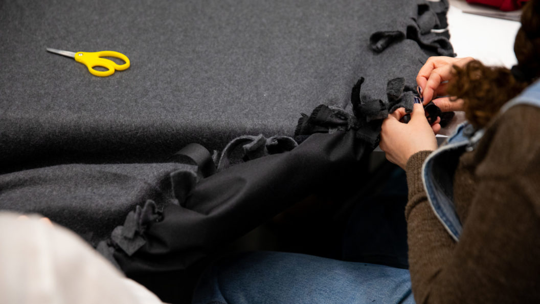 A student sews a blanket together.