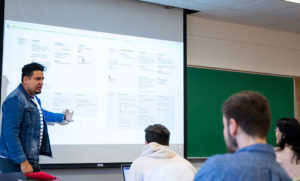 Juan Manuel Menjîvar stands in front of class and teaches his lessons projected on a white screen while studetns look on.