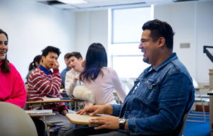 Juan Manuel Menjívar sits and talks with with students in class.