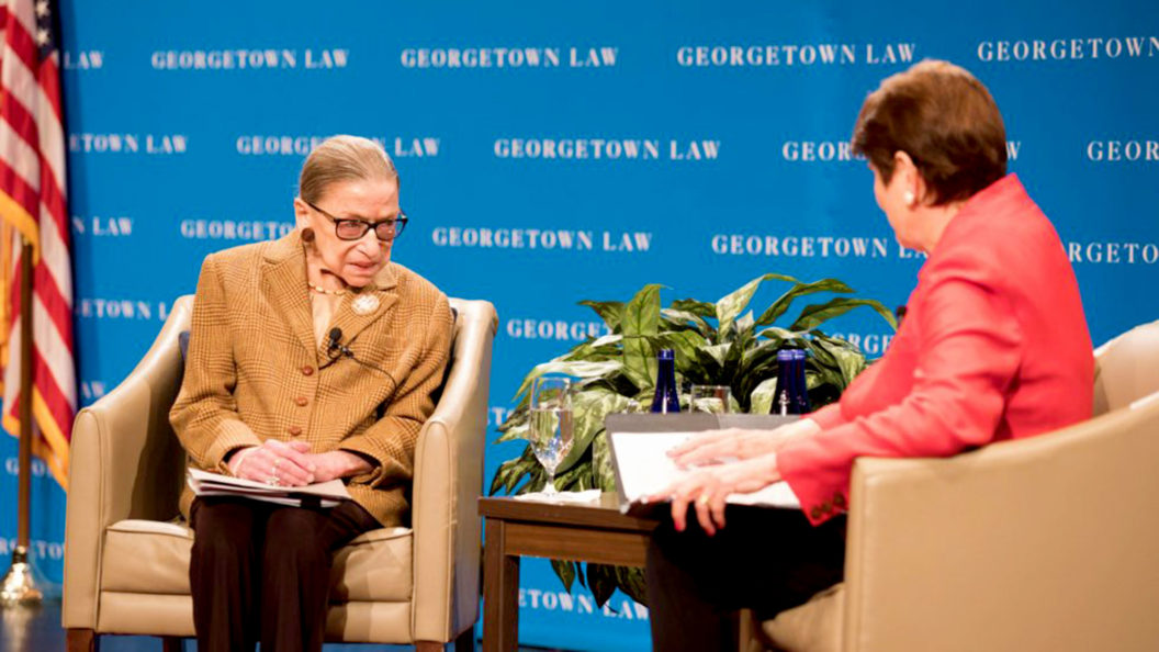 Ruth Bader Ginsburg sits on stage talking to M. Margaret McKeown with blue Georgetown Law signage in the background.