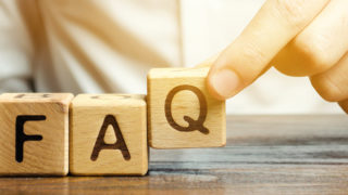 Person puts wooden blocks with the word FAQ (frequently asked questions).