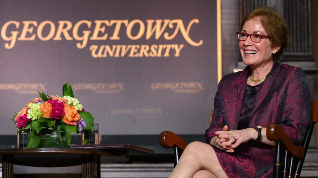 Marie Yovanovitch sits on a stage with her legs crossed in front of a Georgetown banner