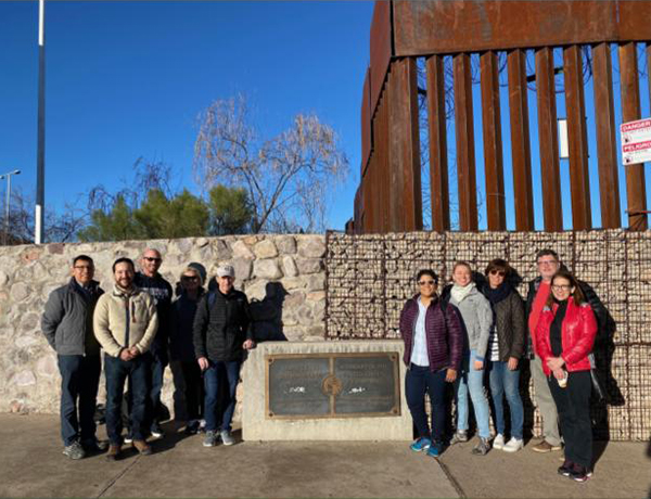 Georgetown faculty and staff stand on either side of a plaque in front of the wall at the border of the U.S. and Mexico