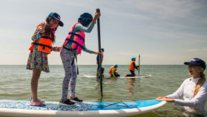 Emi Koch teaches two children how to surf.