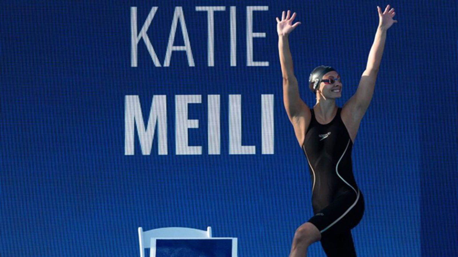 Katie Meili in swimsuit and bathing cap with her arms raised in front of a banner with her name on it