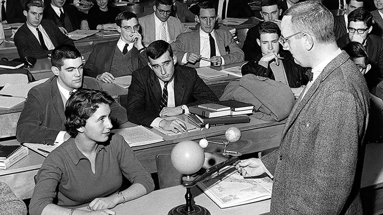 A woman sits in a classroom surrounded by men while the male professor teaches.