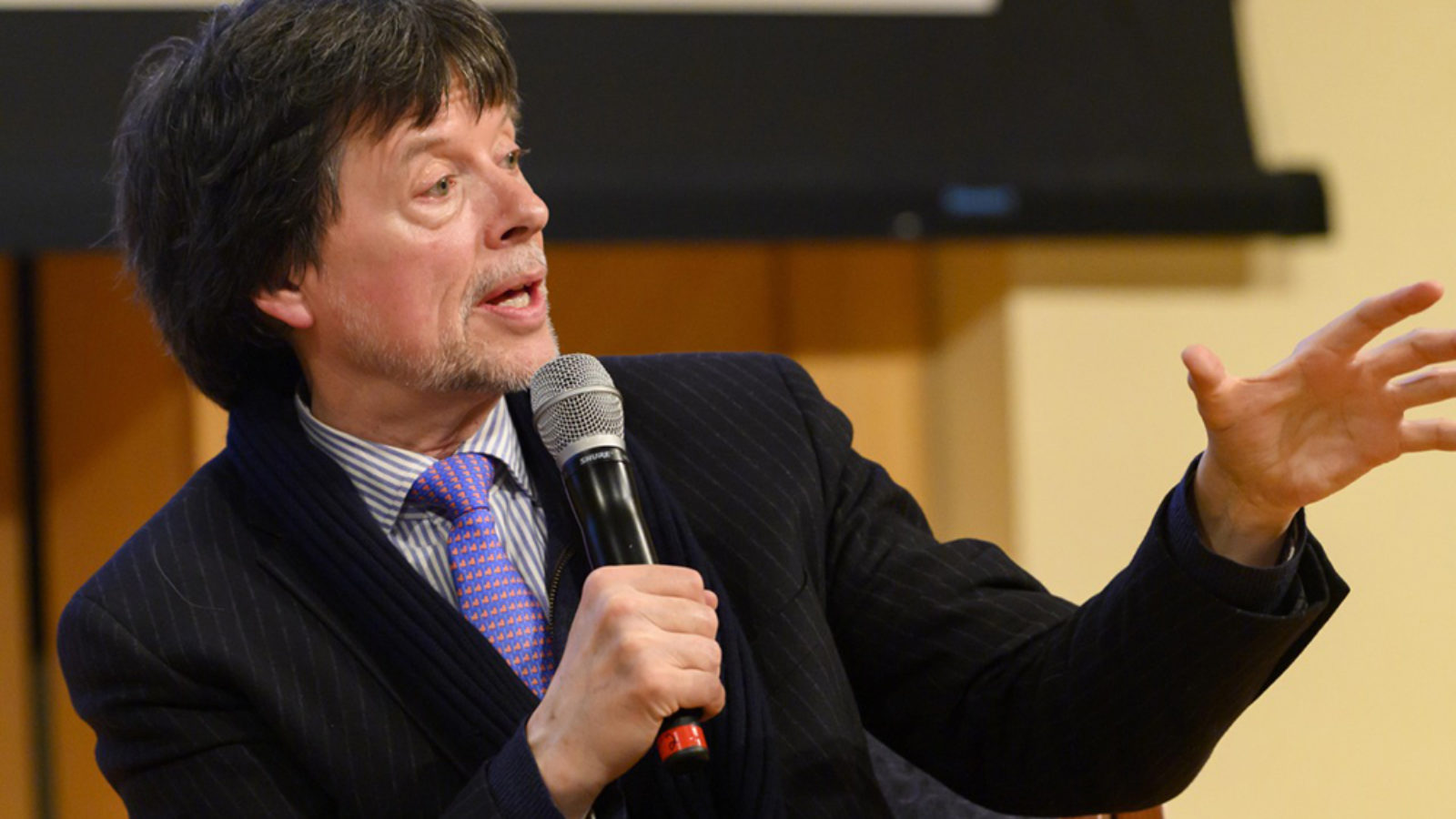 Ken Burns gesturing and holding a microphone