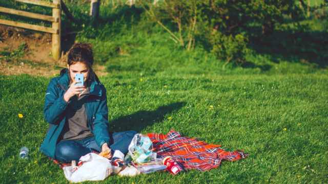 A woman sits outside in the grass chatting by video on her phone.