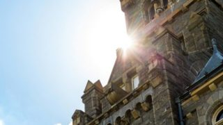 The sun peeks out from the corner of an opening between Healy Hall and the sky.
