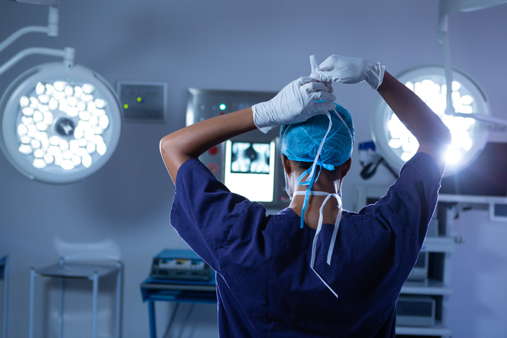 Female surgeon wearing surgical mask on in operating room at hospital