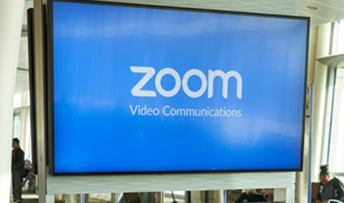 A screen with Zoom video communications on it with people milling around it.