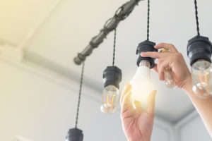 Hands screwing in a hanging light bulb, with other hanging bulbs.