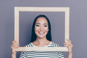 Closeup of young woman holding an empty picture frame in front of her face
