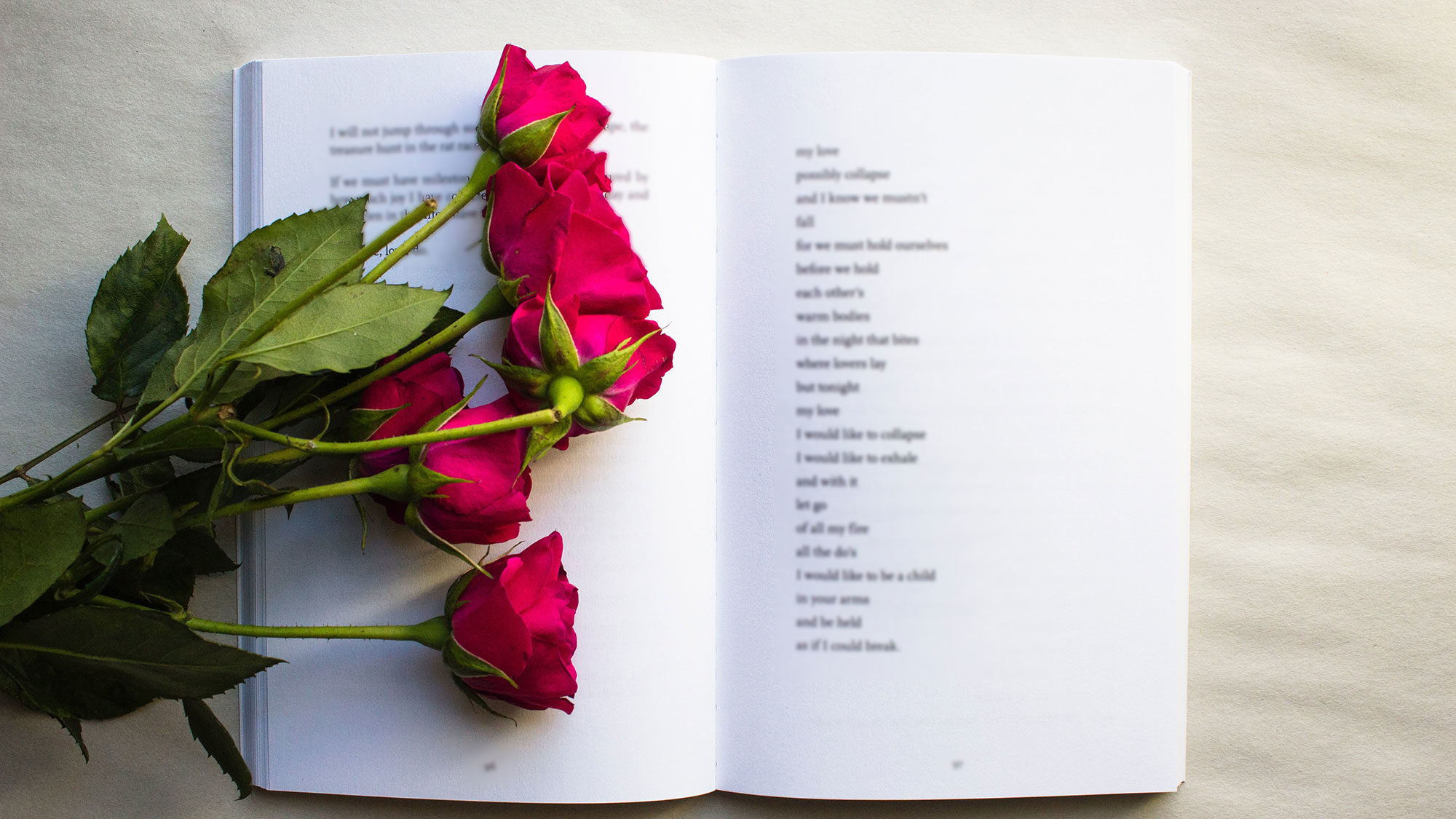 An open book lies flat on a table with the page opened to a poem as red roses lie on the book's page.