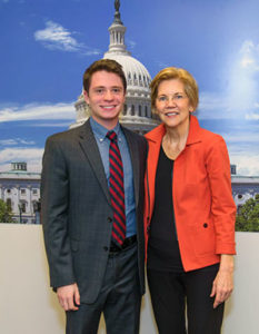 David Yellen and Elizabeth Warren pose together in front of a poster of the U.S. Capitol building.