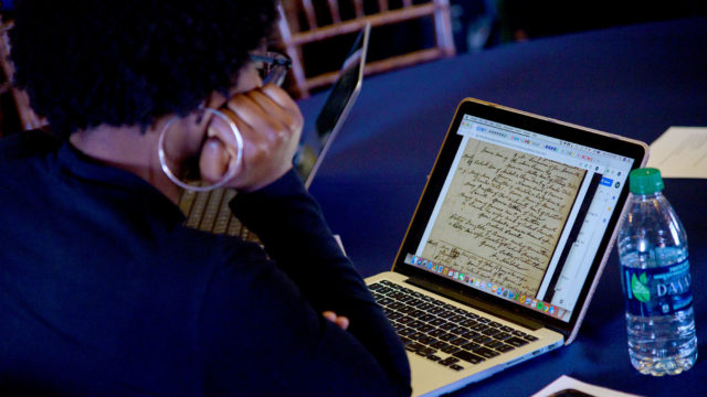 A woman looks at a historical document on her laptop computer.