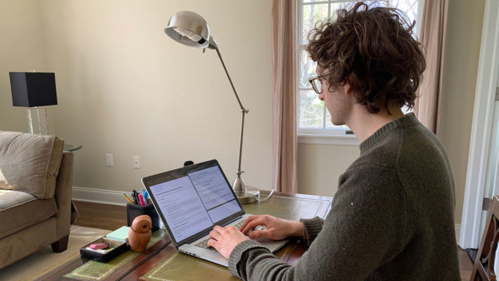 Adrian Hertel sits at a desk typing on his laptop.