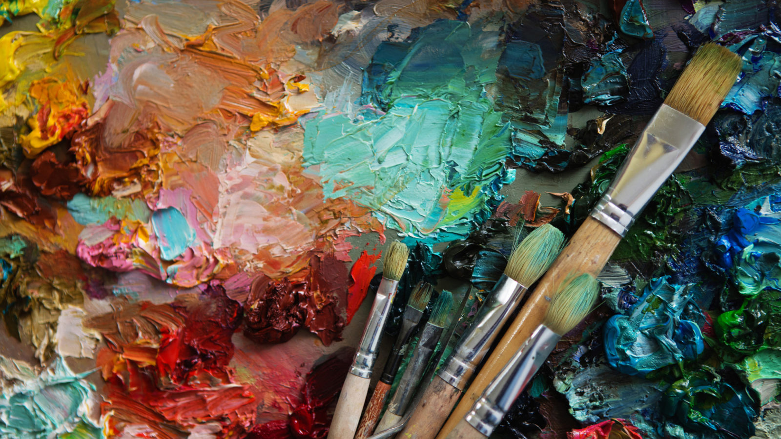 Artists' brushes and oil paints on wooden palette.