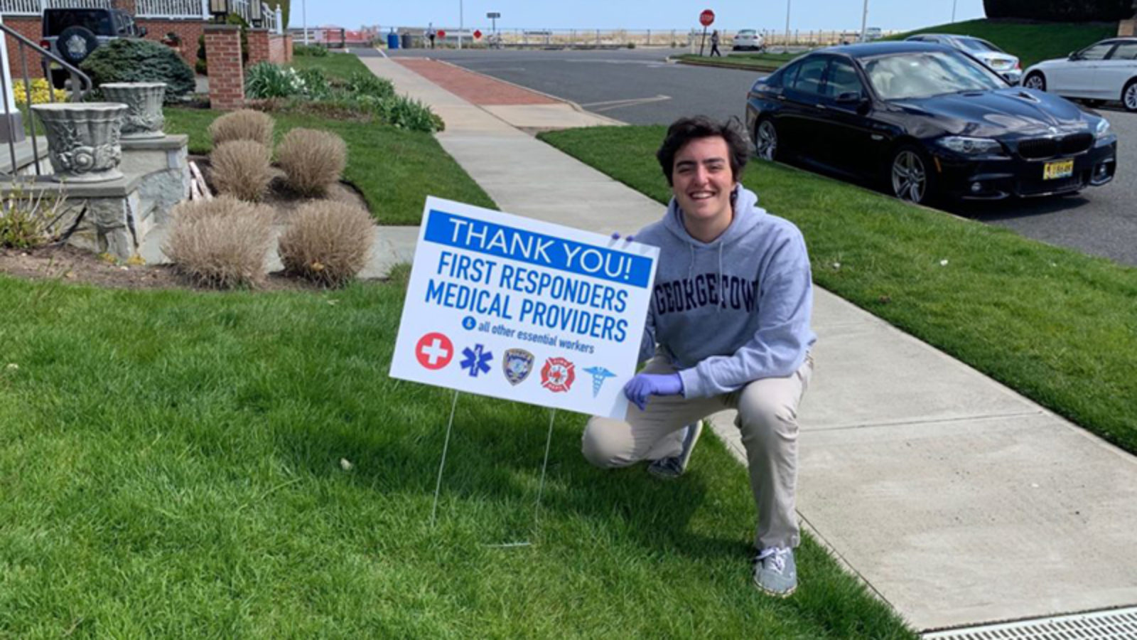 Liam Marshall squatting on a front lawn with a sign stuck in the lawn reading
