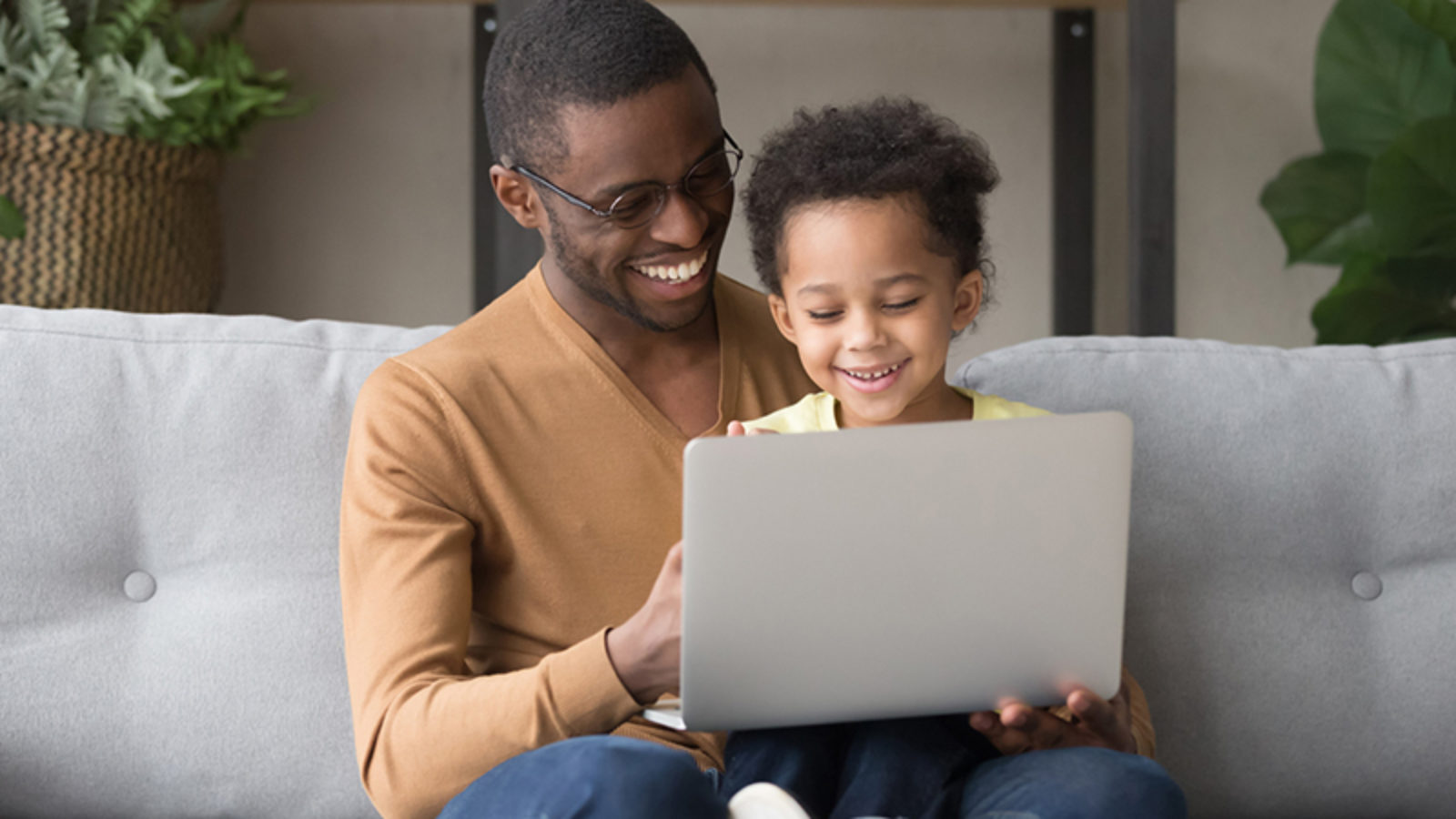 A father sits with a daughter on a sofa with the daughter holding a laptop, both are smiling