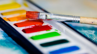 A brush sits atop a pallette of watercolor paint.