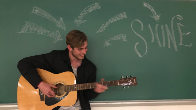Kent Hall playing guitar in front of a black board chalked with arrows pointing toward him and another arrow pointing away from him and the word