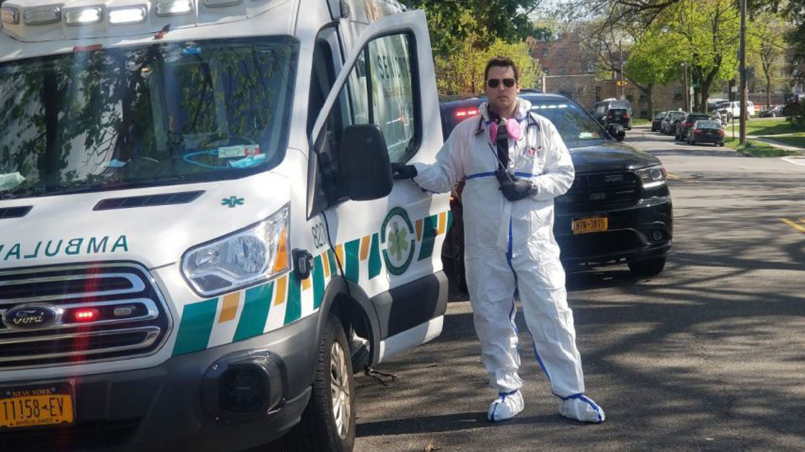 Mark Vatch stands near an emergency medical vehicle dresses in a protective white suit and mask around his neck.