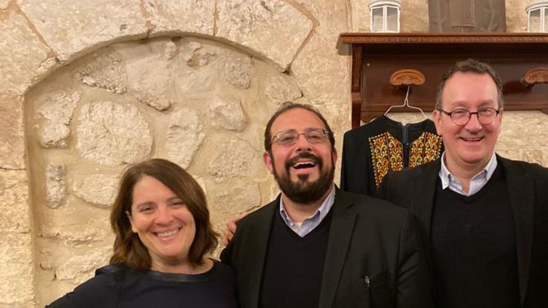 Rachel Gartner, Imam Hendi and Mark Bosco stand in front of a stone archway