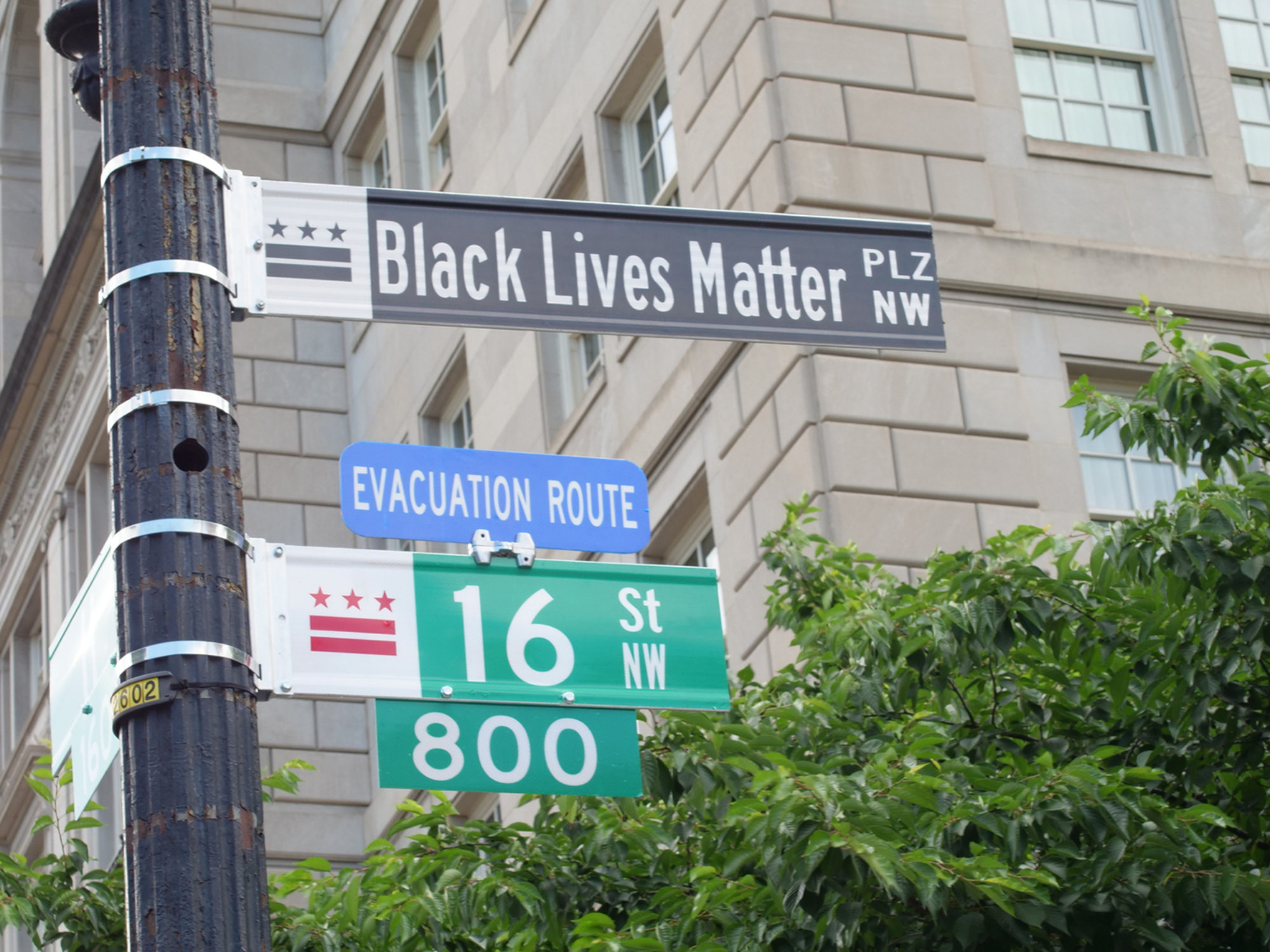 View of a building and street signs that say Black Lives Matter plaza and 16th Street