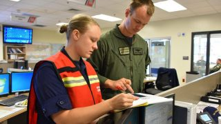 Melissa Cafferty and unidentified man look at a clipboard in an office setting