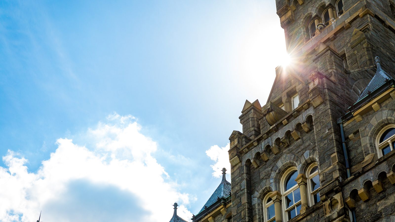 The sun flares from behind the Healy Hall clock tower