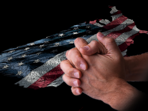 Man holding hands in prayer over USA flag background