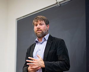 Adam Rothman stands in front of a classroom blackboard