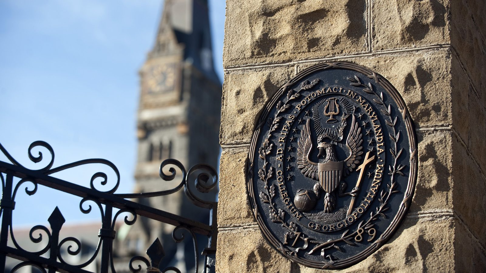 The seal of Georgetown in stone at the gates of the Healy Building, shown in background
