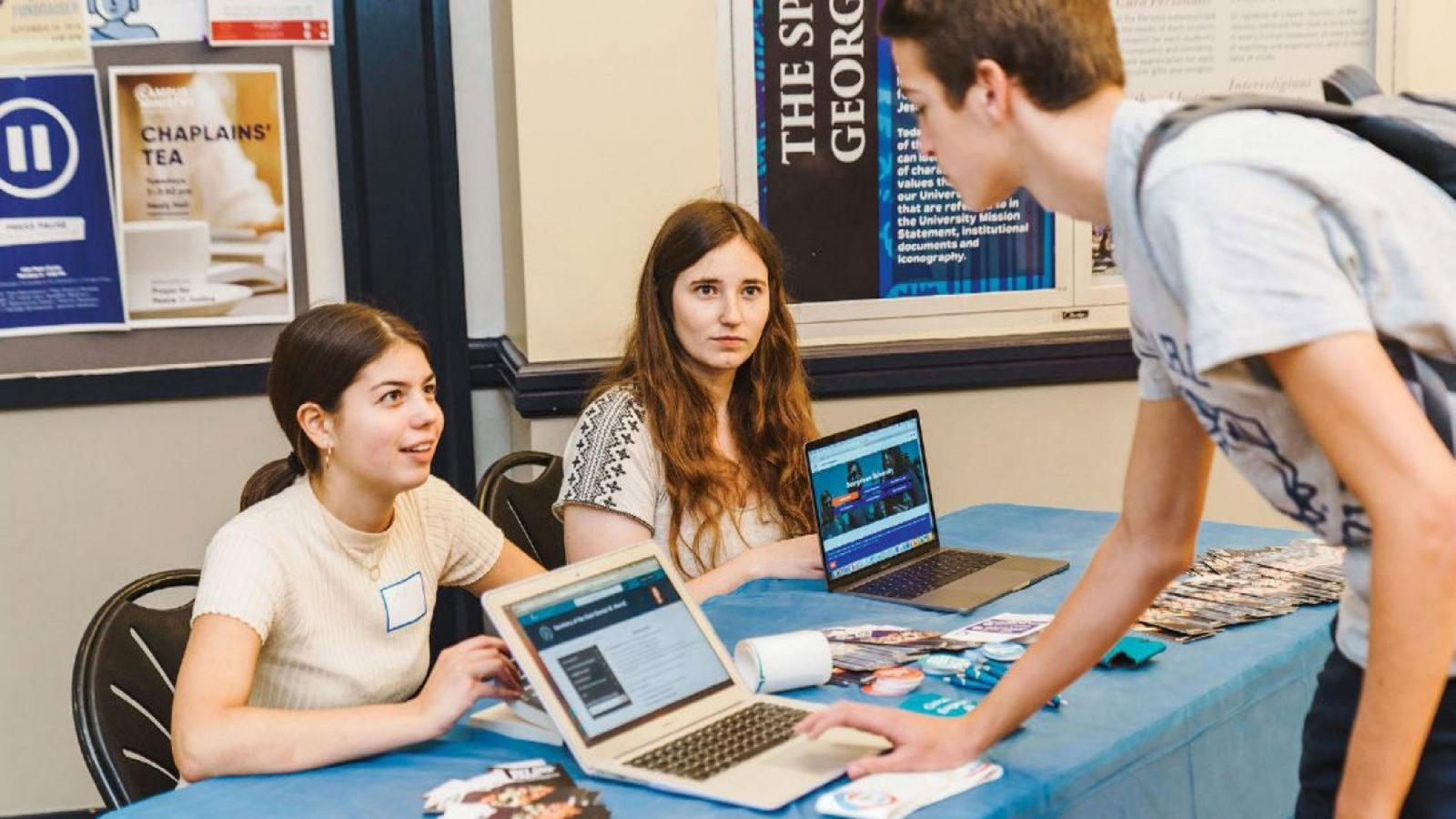 Two students sit at a table while another student registers to vote on a laptop at the table.