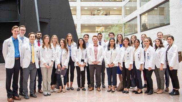 A group of medical students stand together wearing white coats.
