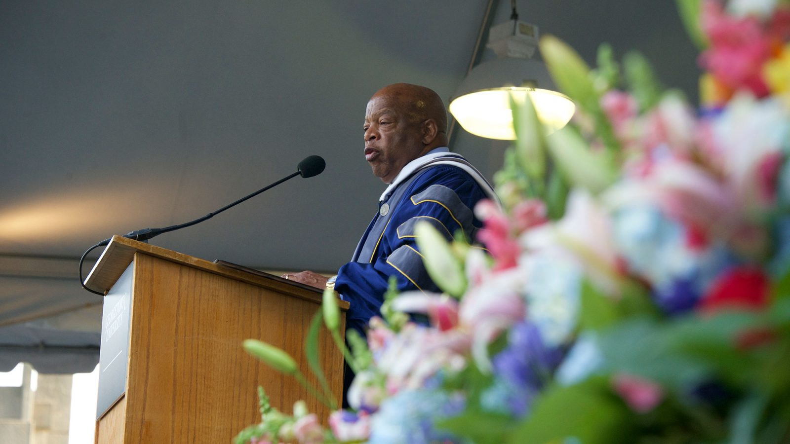 Flowers are in the foreground as John Lewis speaks into the microphone while standing at the lectern in academic regalia.
