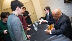 A student looks on as John Lewis signs a book as he sits beside Andrew Aydin.