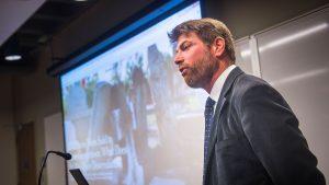 Adam Rothman speaks in front of a projector screen.