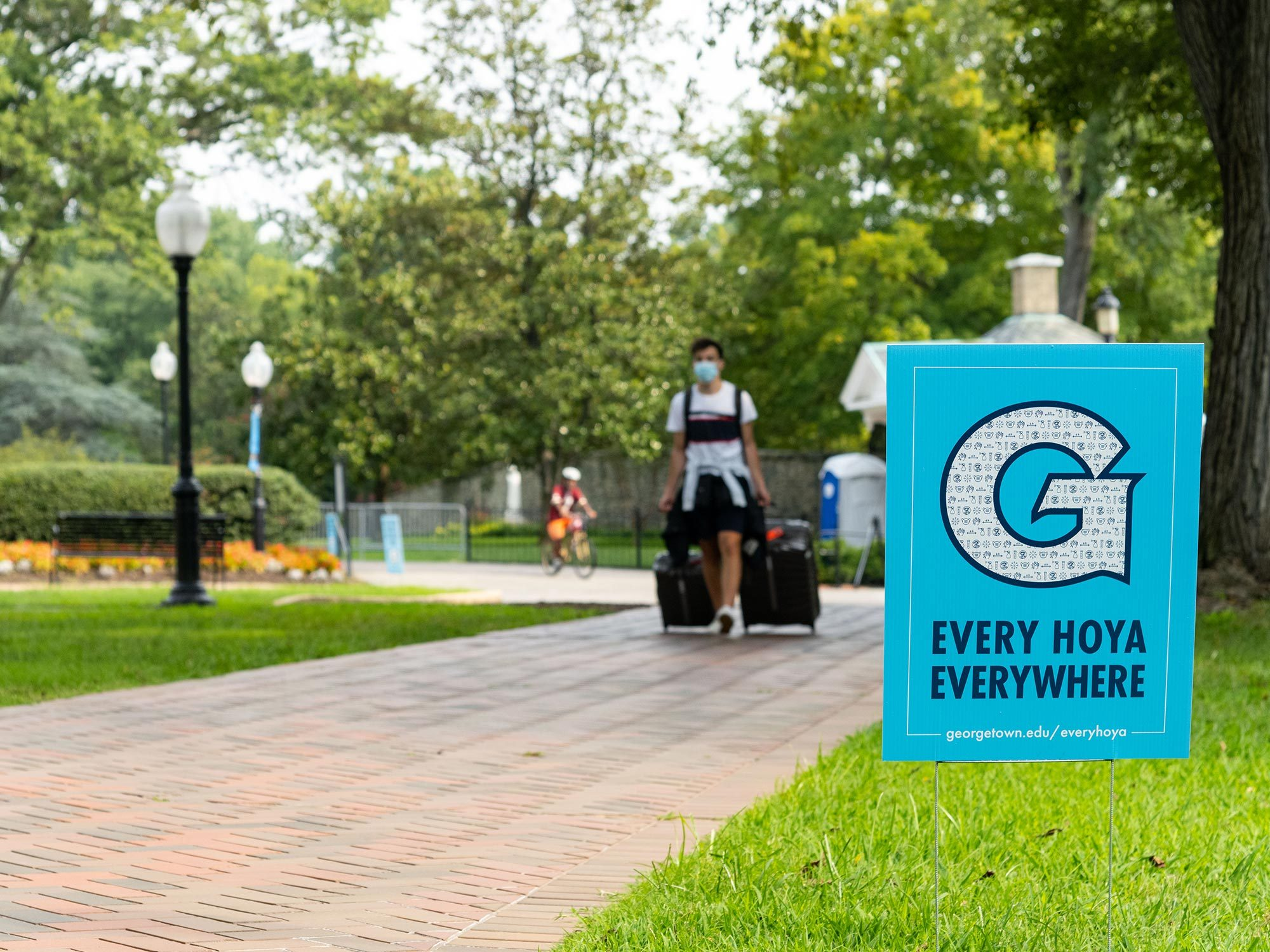 A student pulls his suitcase through campus past a public health sign