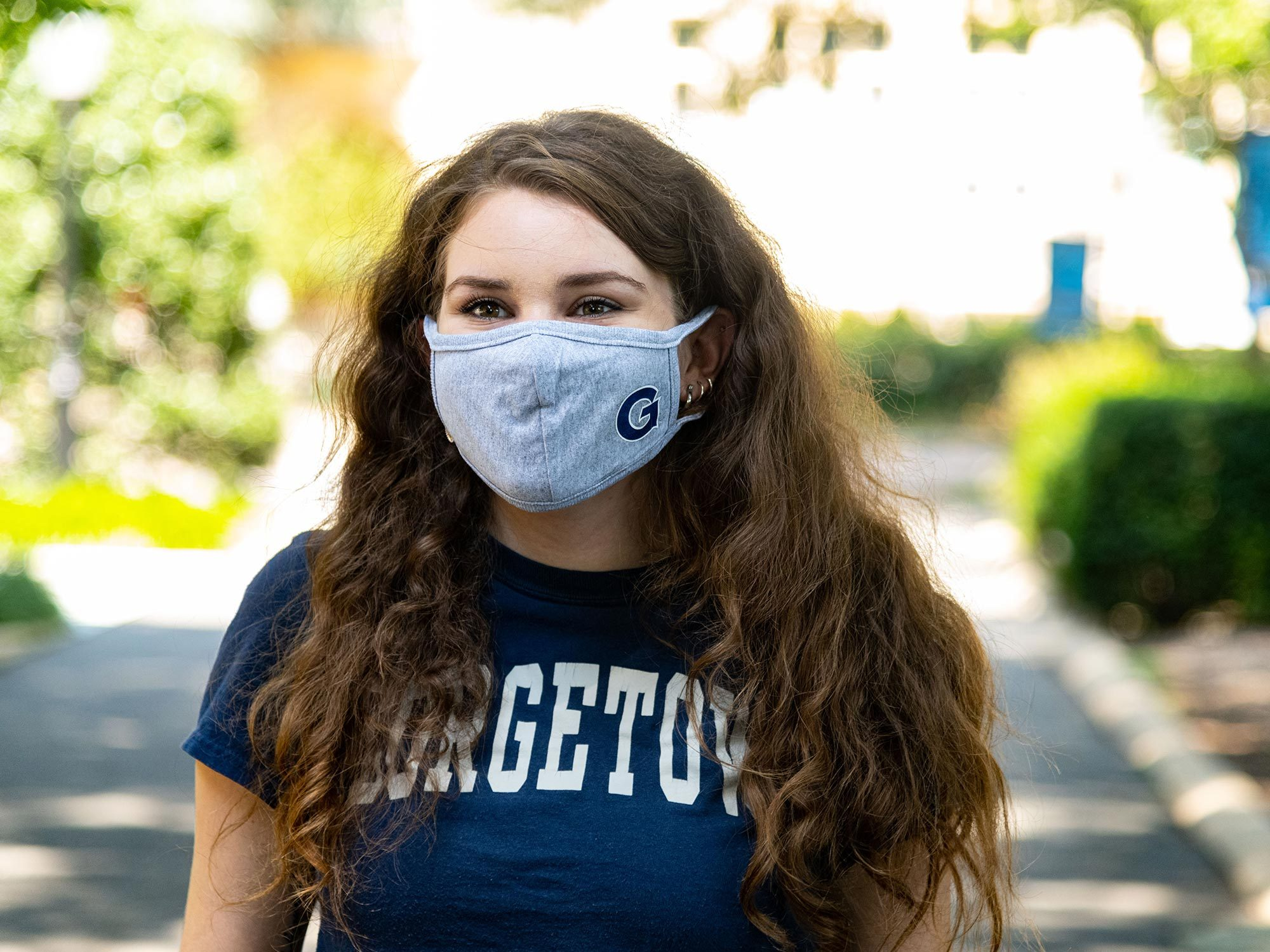 A student wearing a mask looks into the camera