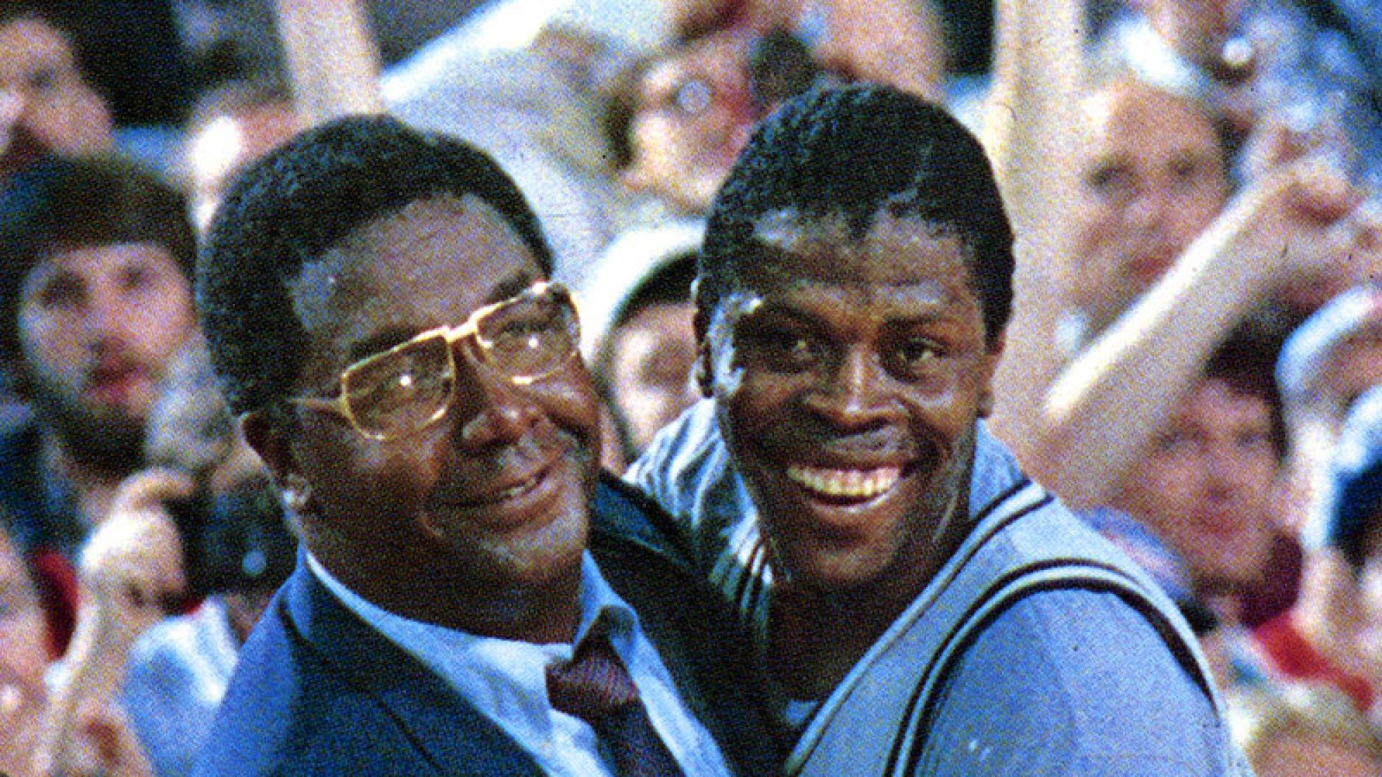 John Thompson Jr. and Patrick Ewing embrace in celebration on the court after a game.