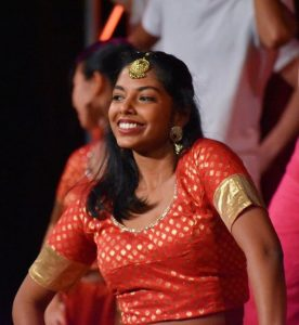 Ashanee Kottage dances on stage during Rangila wearing a read and gold costume.