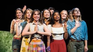 Ashanee Kottage stands in the middle of the front row of a group of women acting on stage.