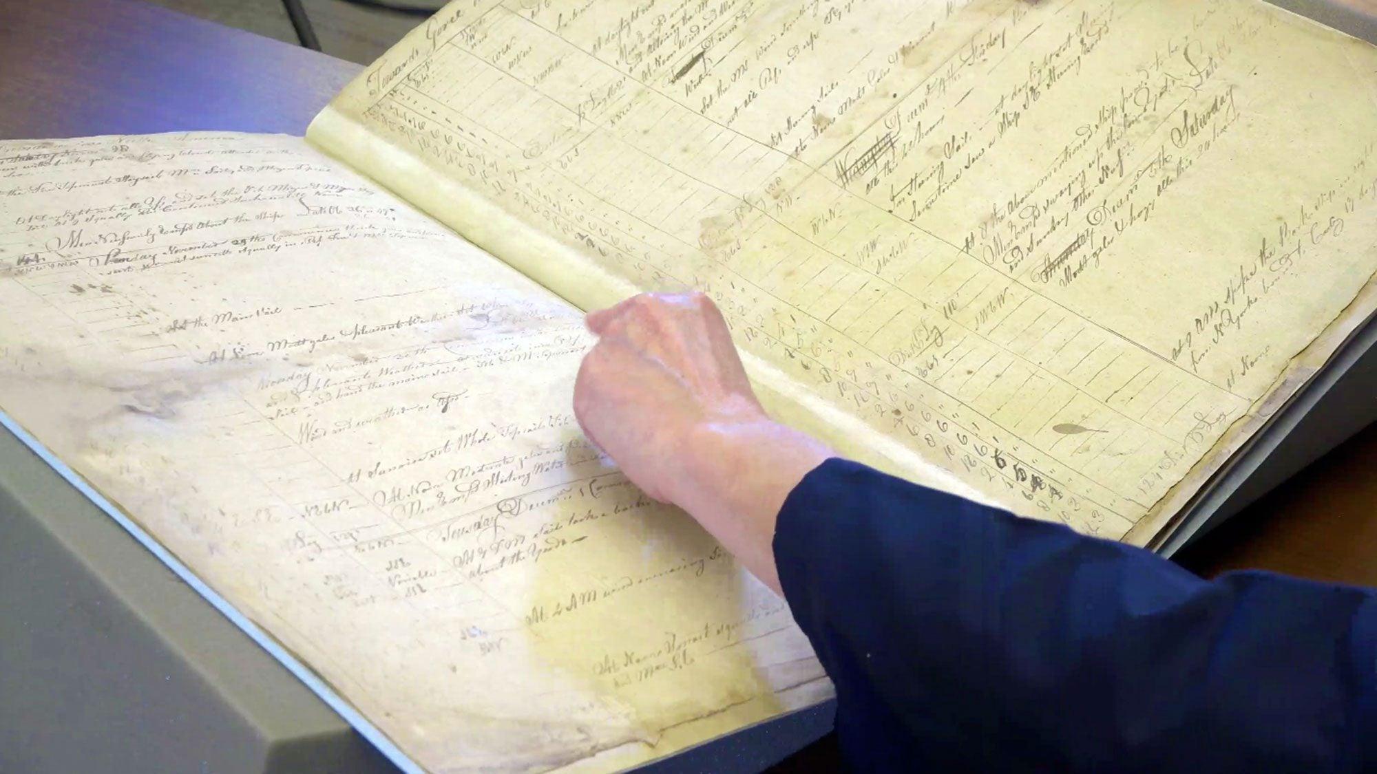 A woman flips through an old ship's logbook.