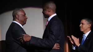 John Thompson embraces Dikembe Mutombo as Barack Obama looks on and applauds the two men.