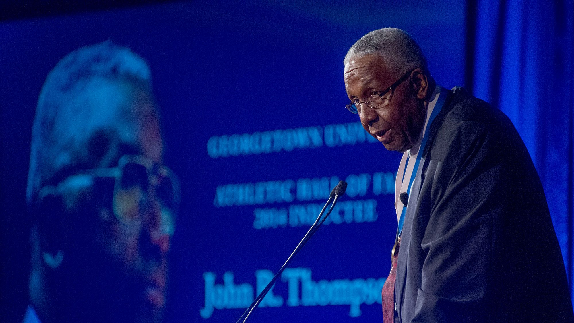 John Thompson Jr. stands on stage with a tribute to him projected in the background.