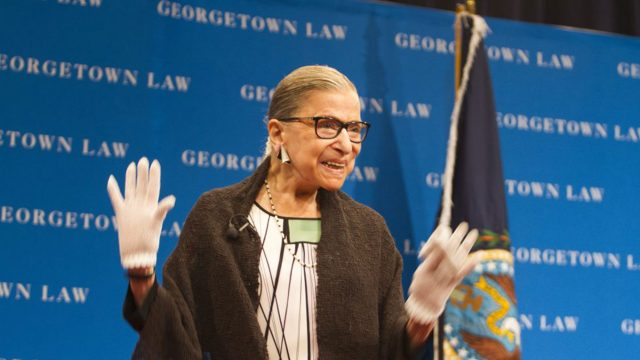 Ruth Bader Ginsburg stands on stage waving to the audience with both hands with a Georgetown Law background.