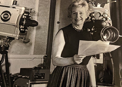 Lillian Brown standing and holding some papers in front of two CBS cameras in the late 1960s.