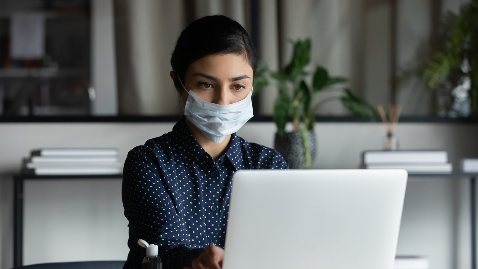 Young woman sitting at a desk wearing a mask and working on a computer